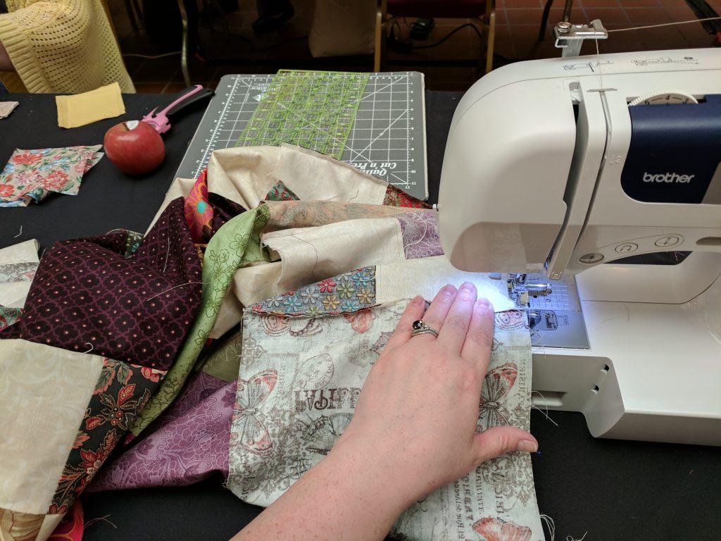 rining fabric through a sewing machine.